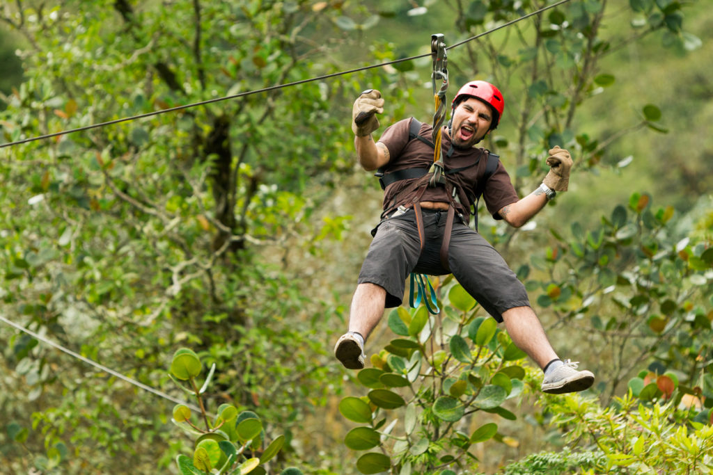 Man experiencing the thrill of a tree top adventure