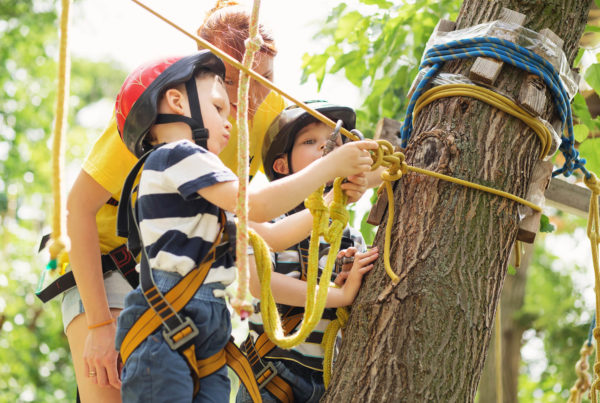 Two boys at an adventure park inspecting a rope with an instructor